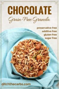chocolate grain free granola in a bowl over a blue cloth napkin