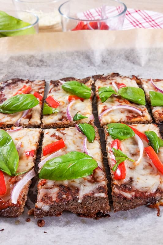 Low-carb meatza keto pizza sliced on baking paper