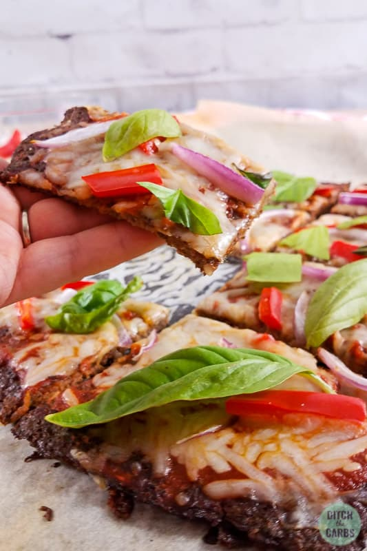 Low-carb meatza keto pizza sliced and lifted with hands