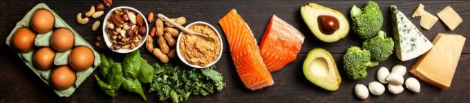 low carb foods on a black background including eggs, nuts, salmon, veggies, and cheese.
