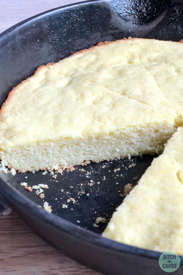 A close up shot of keto cornbread still in the cast-iron skillet. The cornbread has been sliced into triangle and one piece is missing.